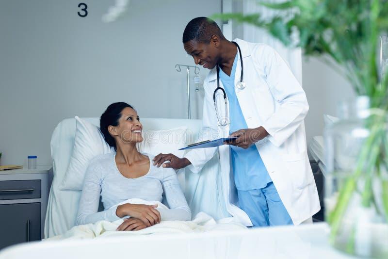 Mannelijke arts die met vrouwelijke patiënt in de afdeling interactie aangaan stock fotografie