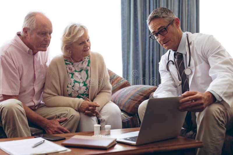 Mannelijke arts die over laptop met hoger paar bij pensioneringshuis bespreken stock fotografie