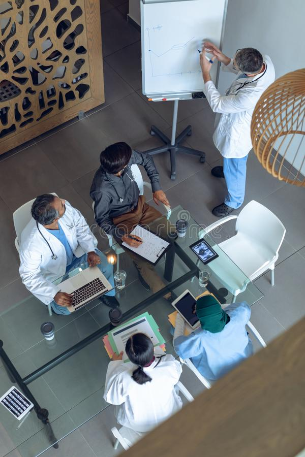 Mannelijke arts die over tikgrafiek in vergadering bij het ziekenhuis verklaren royalty-vrije stock fotografie