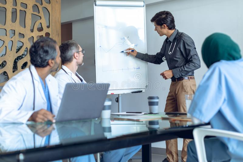Mannelijke arts die over tikgrafiek in vergadering bij het ziekenhuis verklaren stock afbeeldingen