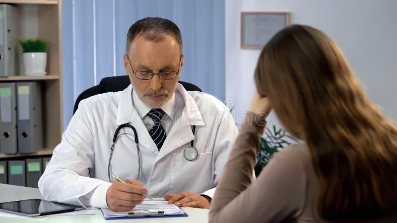 Mannelijke arts die patiënt informeren over hoge kosten van chirurgie, vrouw in wanhoop stock afbeelding