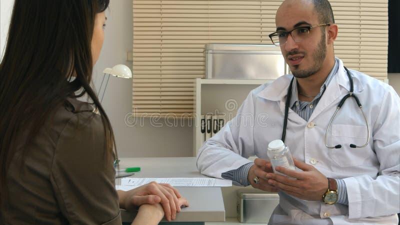 Mannelijke arts die pillen voorschrijven aan vrouwelijke patiënt en bijwerkingen verklaren stock foto's