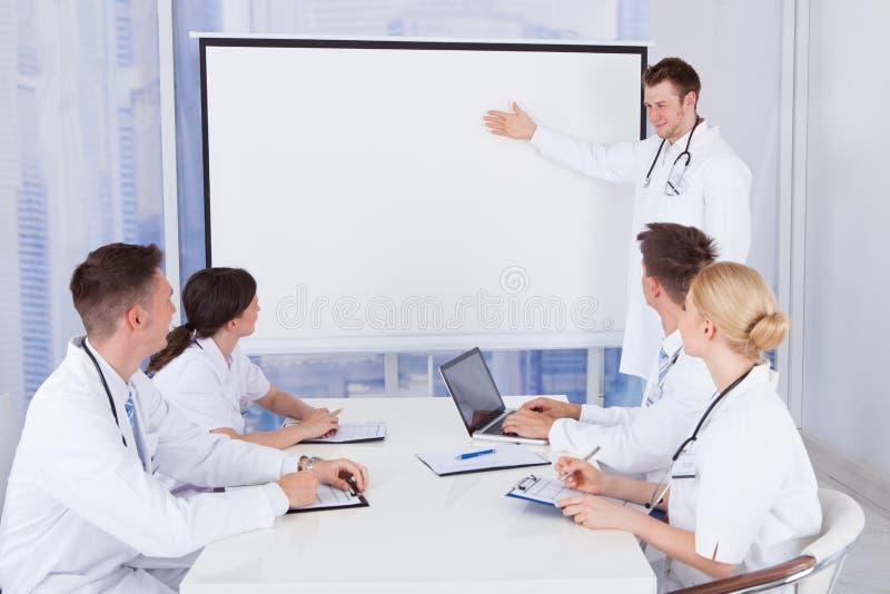 Mannelijke arts die presentatie geven aan collega's in het ziekenhuis stock foto's