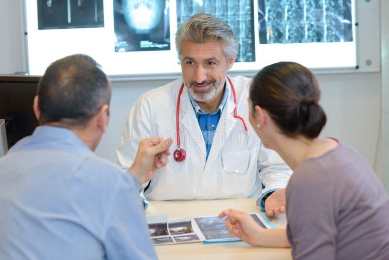 Mannelijke arts die x-ray resultaten tonen om in kliniek te koppelen royalty-vrije stock foto's