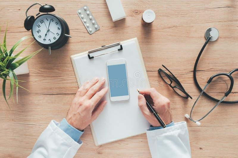 Mannelijke arts het schrijven nota's over klemborddocument tijdens medisch examen stock foto's