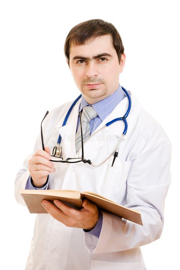 Mannelijke arts met een stethoscoop en een boek stock afbeelding