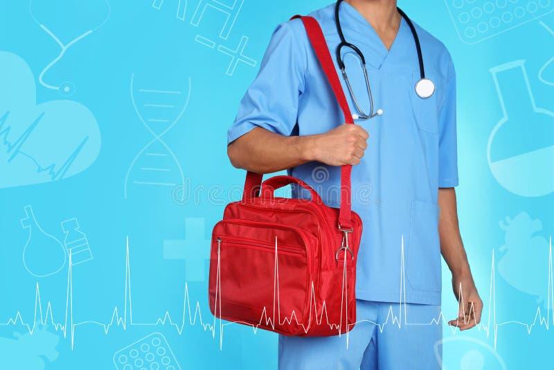 Mannelijke arts met eerste hulpuitrusting en ruimte voor tekst op kleurenachtergrond Medisch voorwerp stock foto's