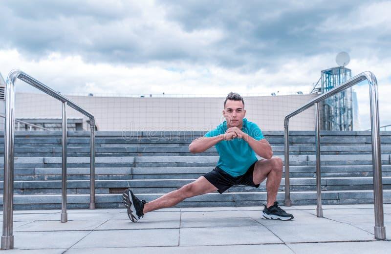 Mannelijke atleet, in de zomer in de stad, die de spieren uitrekken vóór het aanstoten, geschiktheid opleiding, sportkleding, con stock afbeeldingen