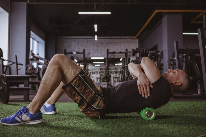 Mannelijke atleet die schuimrol met behulp van bij de gymnastiek royalty-vrije stock foto