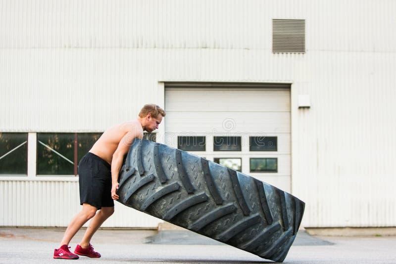 Mannelijke Atleet Flipping Large Tire royalty-vrije stock foto's