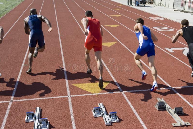 Mannelijke Atleten die van Startblok lopen stock fotografie