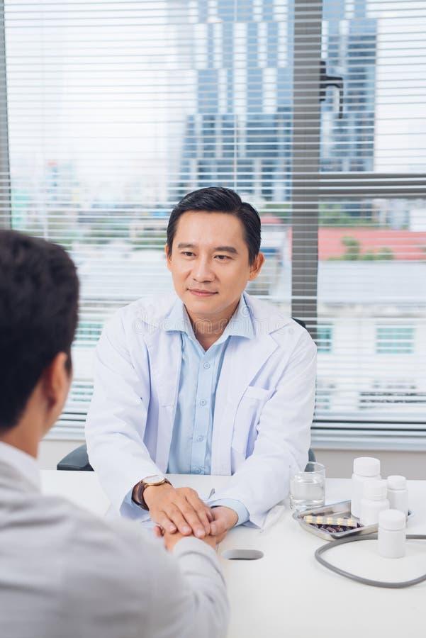 Mannelijke Aziatische artsen troostende patiënt bij het raadplegen van ruimte stock afbeelding