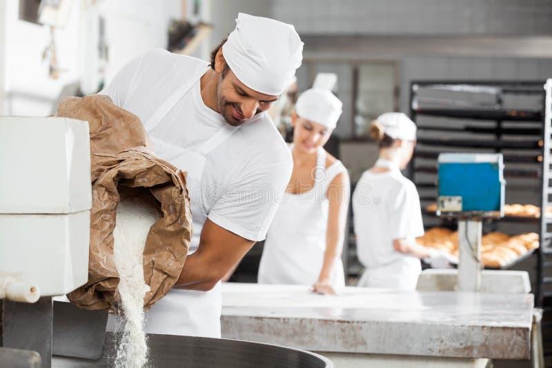 Mannelijke Baker Pouring Flour In het Kneden Machine stock fotografie