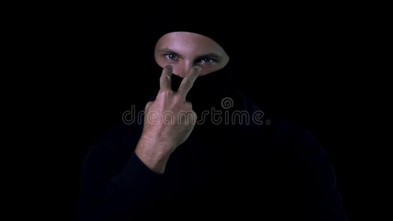 Mannelijke bandieten zwarte balaclava die het letten tonen op u ondertekent, persoonlijke veiligheid, gevaar stock afbeelding