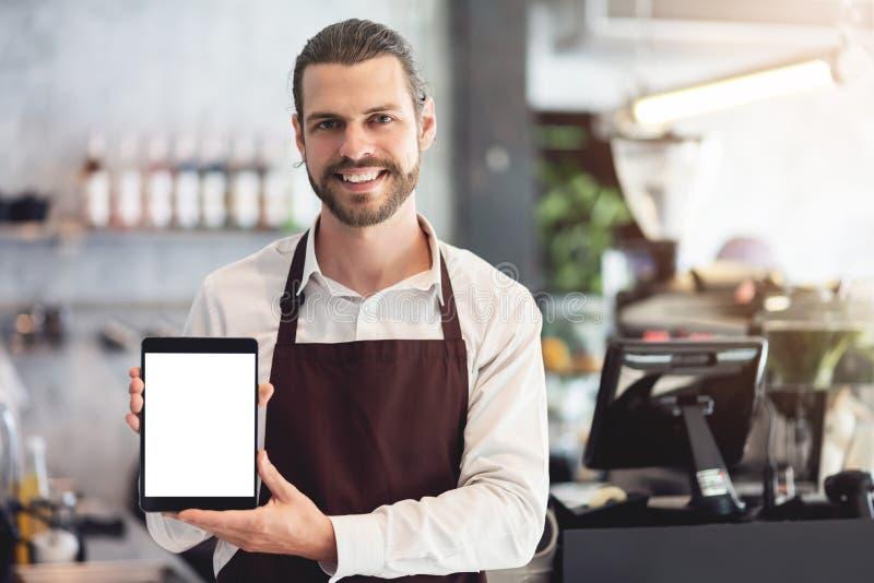 Mannelijke barista die en een digitale tablet houden tonen royalty-vrije stock afbeelding