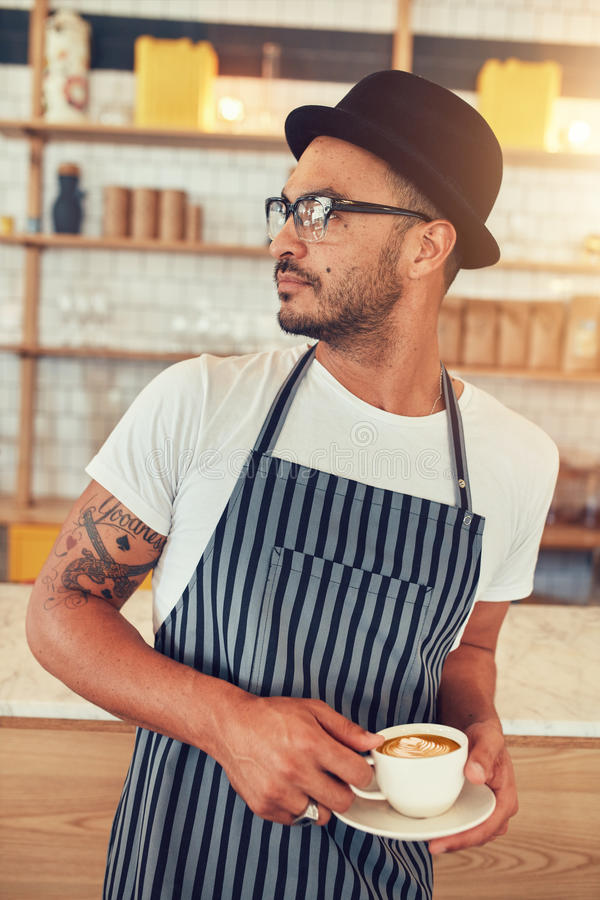 Mannelijke barista die zich bij koffiewinkel bevinden stock fotografie