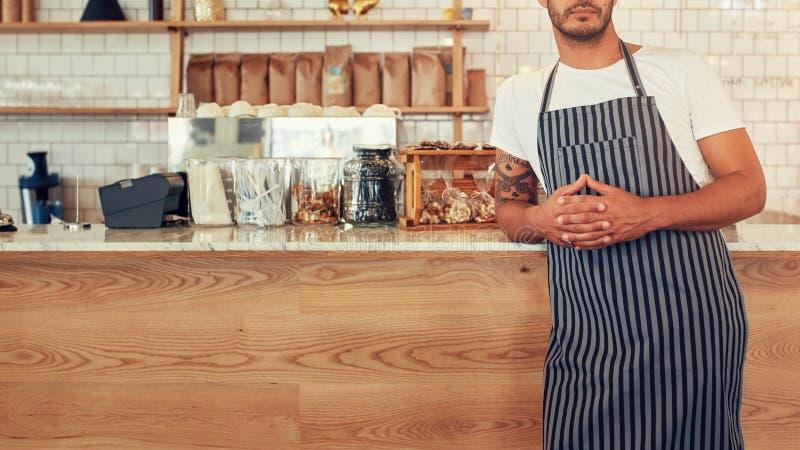 Mannelijke barista die zich bij koffiewinkel bevinden stock foto