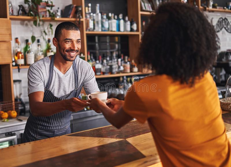 Mannelijke barista dient koffiekop aan vrouwelijke klant in koffie stock afbeeldingen
