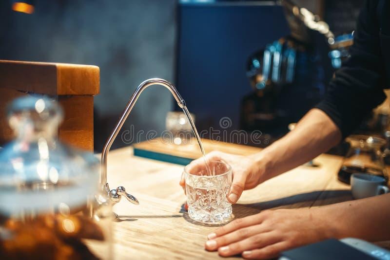 Mannelijke barista giet gefiltreerd water in het glas royalty-vrije stock afbeelding