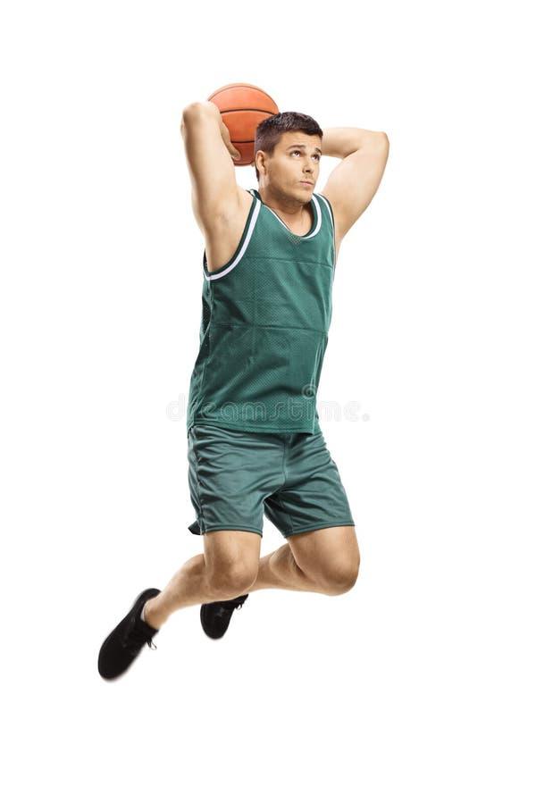 Mannelijke basketbalspeler die in actie met een bal en het springen schiet stock foto
