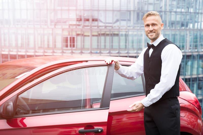 Mannelijke Bediende Opening Car Door stock afbeeldingen