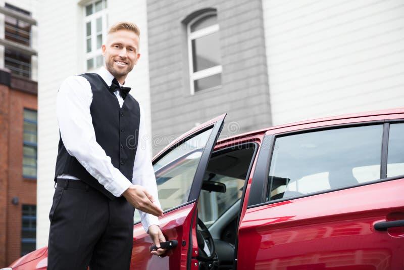 Mannelijke Bediende Opening Car Door stock foto