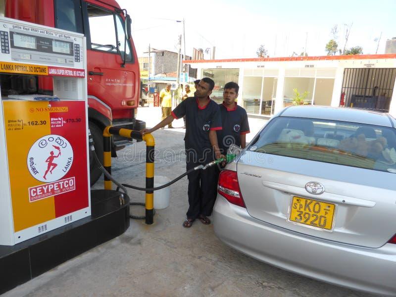 Mannelijke begeleidende het vullen auto bij benzinepomp stock foto's
