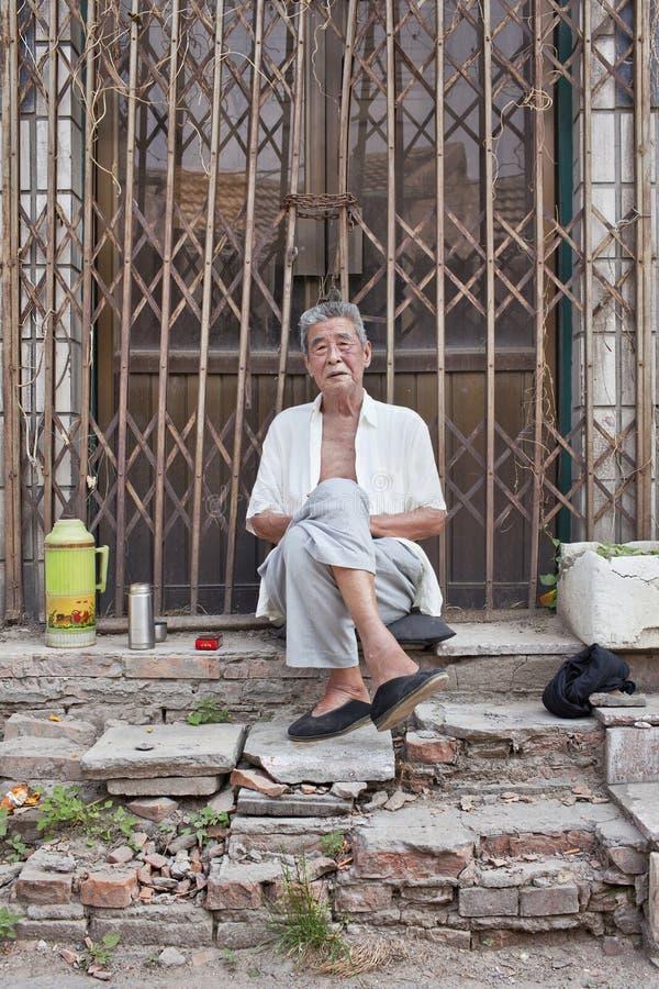 Mannelijke bejaarden in een hutong, Peking, China stock foto