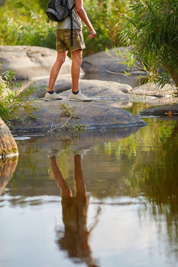 Mannelijke benen die bij bergpiek wandelen Trekkingsschoenen op wandelaarvoeten die in openlucht rotsstenen op rivierkreek kruise stock afbeeldingen