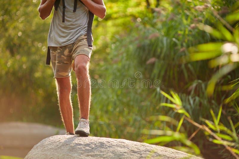 Mannelijke benen die bij bergpiek wandelen Trekkingsschoenen op wandelaarvoeten die in openlucht rotsstenen op rivierkreek kruise royalty-vrije stock foto's
