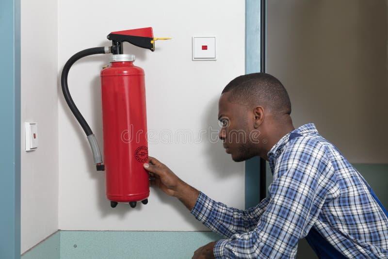 Mannelijke Beroeps die een Brandblusapparaat controleren royalty-vrije stock afbeelding