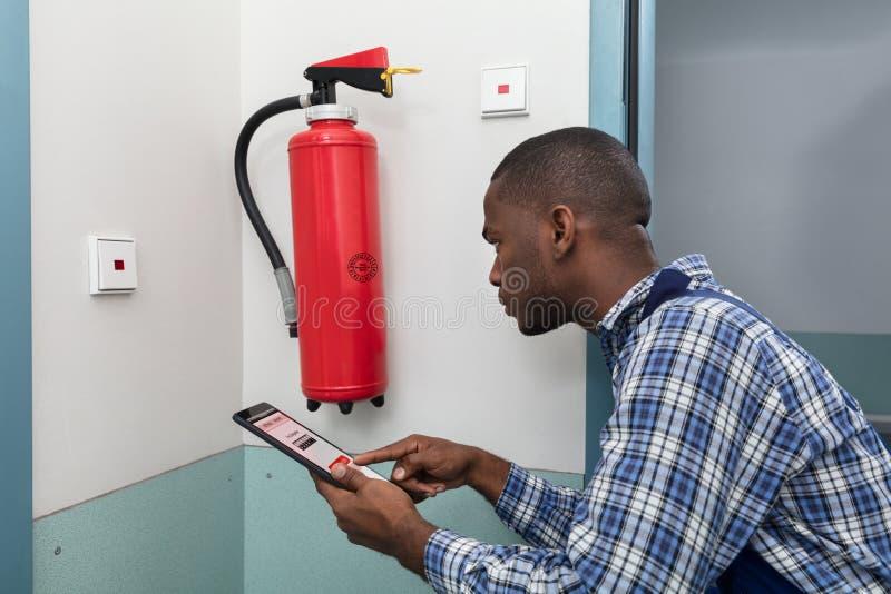 Mannelijke Beroeps die een Brandblusapparaat controleren royalty-vrije stock foto