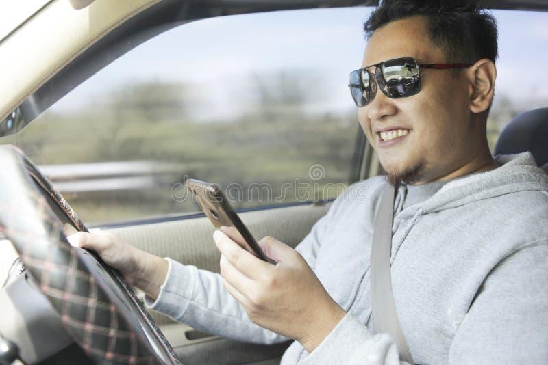 Mannelijke Bestuurder Reading Message op Smartphone terwijl het Drijven van een Auto royalty-vrije stock fotografie
