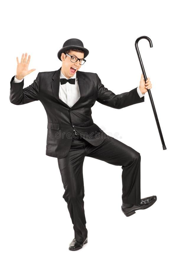 Mannelijke blijspelacteur die met een riet dansen stock foto's
