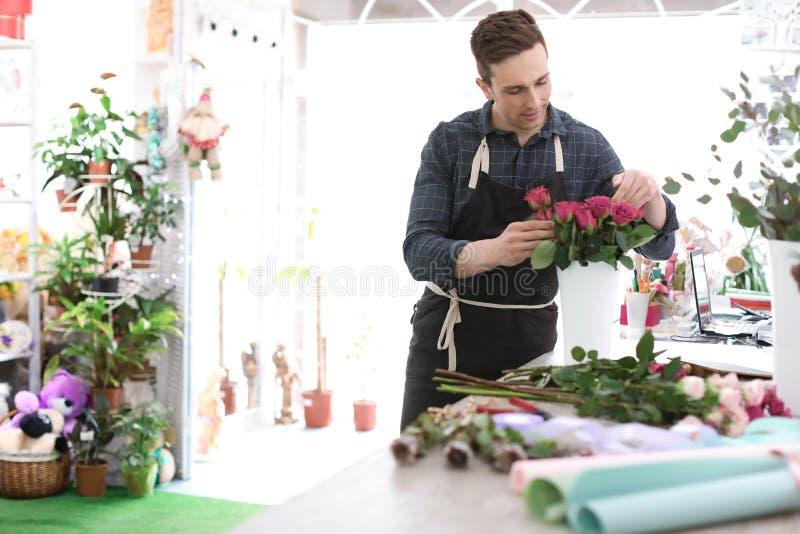 Mannelijke bloemist die mooi boeket in winkel creëren royalty-vrije stock afbeeldingen