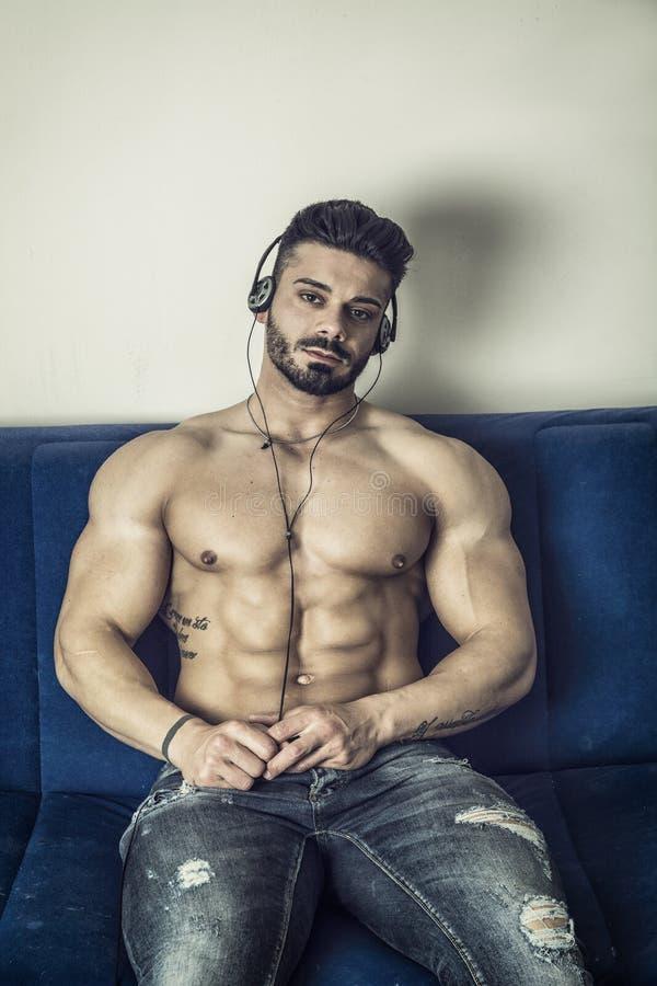 Mannelijke bodybuilder die aan muziek op bank luisteren stock foto's