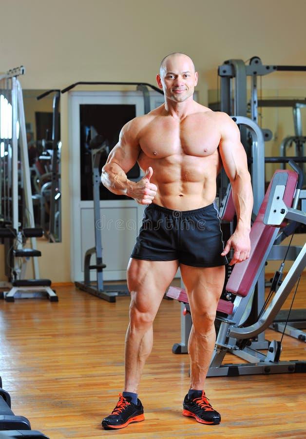 Mannelijke bodybuilder die duimen in gymnastiek toont stock afbeelding