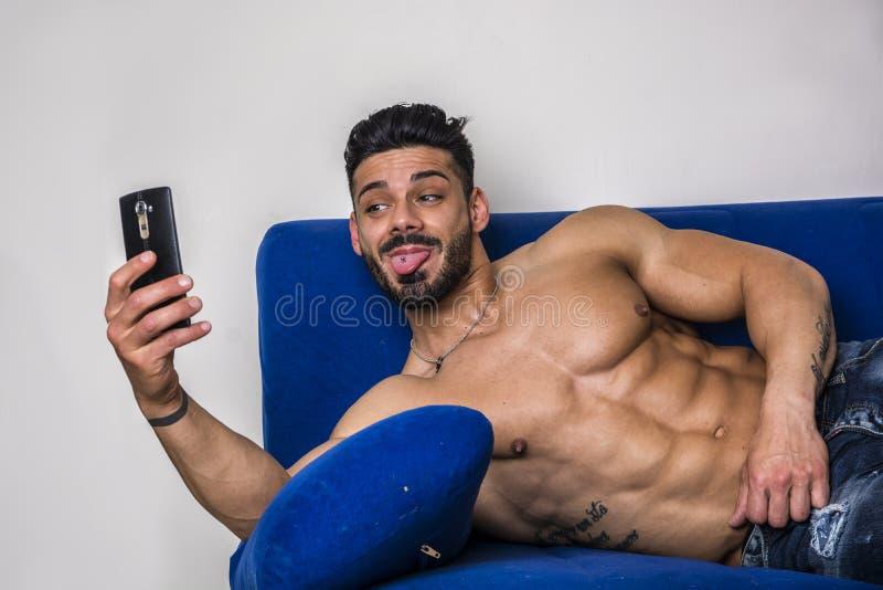 Mannelijke bodybuilder die selfie foto op bank nemen stock afbeeldingen