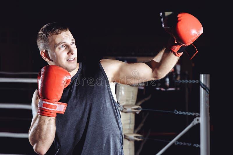 Mannelijke bokser die een selfie op zijn smartphone na opleiding nemen stock afbeeldingen