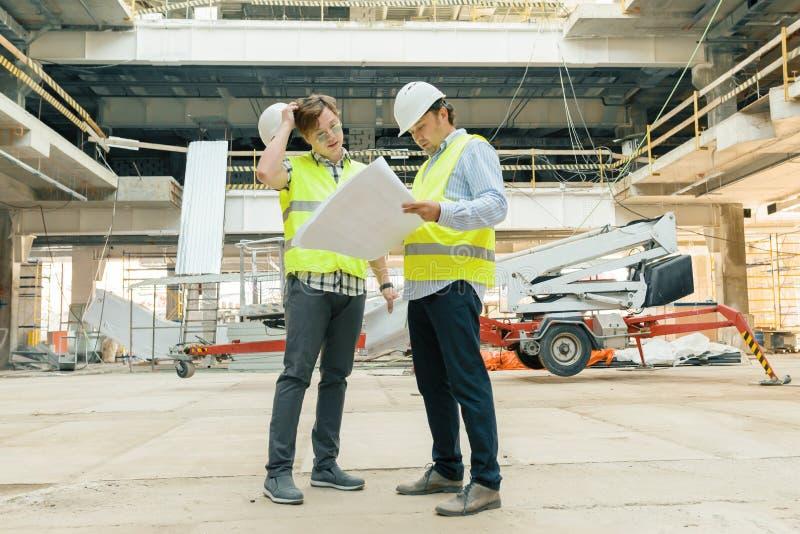 Mannelijke bouwarbeiders die bij bouwwerf, bouwers werken die in blauwdruk kijken De bouw, ontwikkeling, groepswerk en mensen stock foto