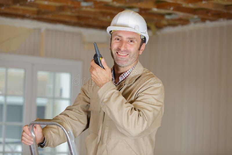 Mannelijke bouwer in bouwvakker met walkie-talkie royalty-vrije stock afbeeldingen