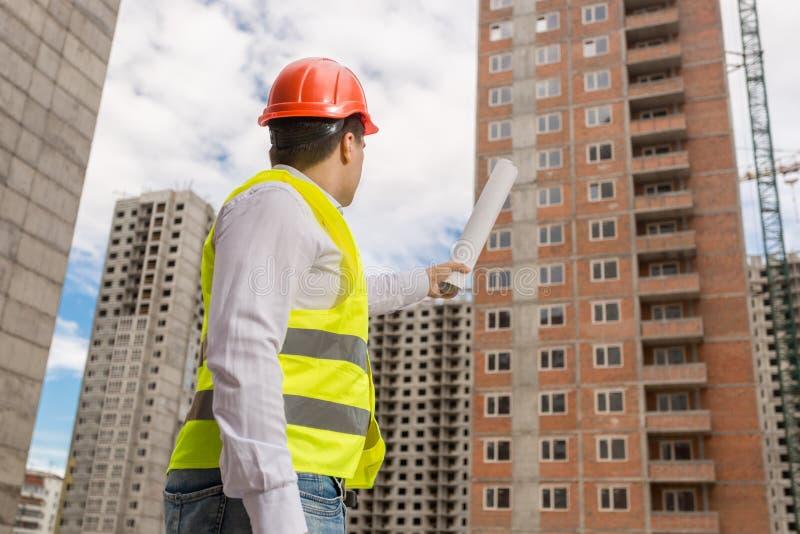 Mannelijke bouwvakker in de blauwdrukken van de bouwvakkerholding en het richten op in aanbouw de bouw stock fotografie