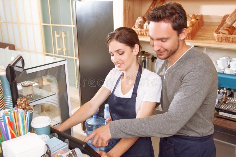 Mannelijke cafetariaarbeider die zijn vrouwelijke collega helpen royalty-vrije stock afbeelding
