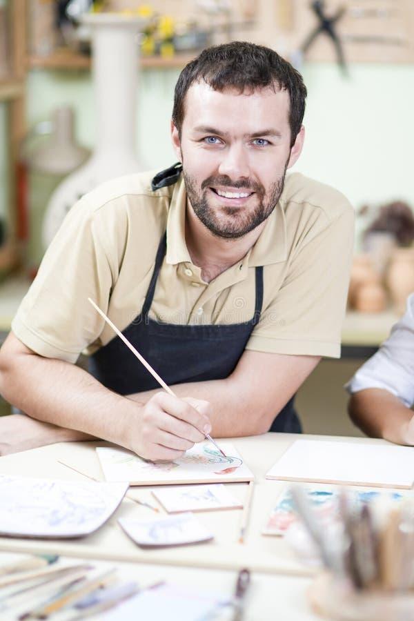 Mannelijke Ceramist Gebruikend Penseel voor Verglazing en Schilderend Keramiek stock foto's
