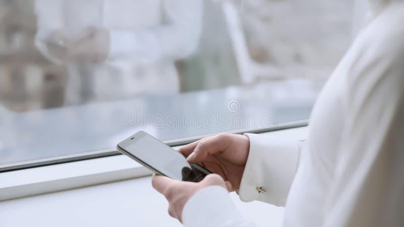 Mannelijke chef- het scrollen touchscreen op smartphone, lezingennieuws, vensterbezinning royalty-vrije stock foto's