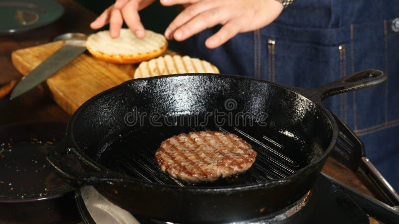 Mannelijke chef-kok in blauwe schort bradende kotelet op een pangrill dichtbij andere ingrediënten voor het maken van hamburgers  royalty-vrije stock afbeelding