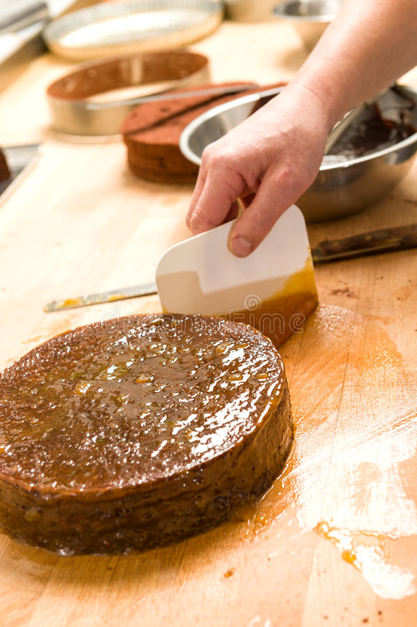 Mannelijke chef-kok die chocoladecake in keuken verfraaien royalty-vrije stock foto