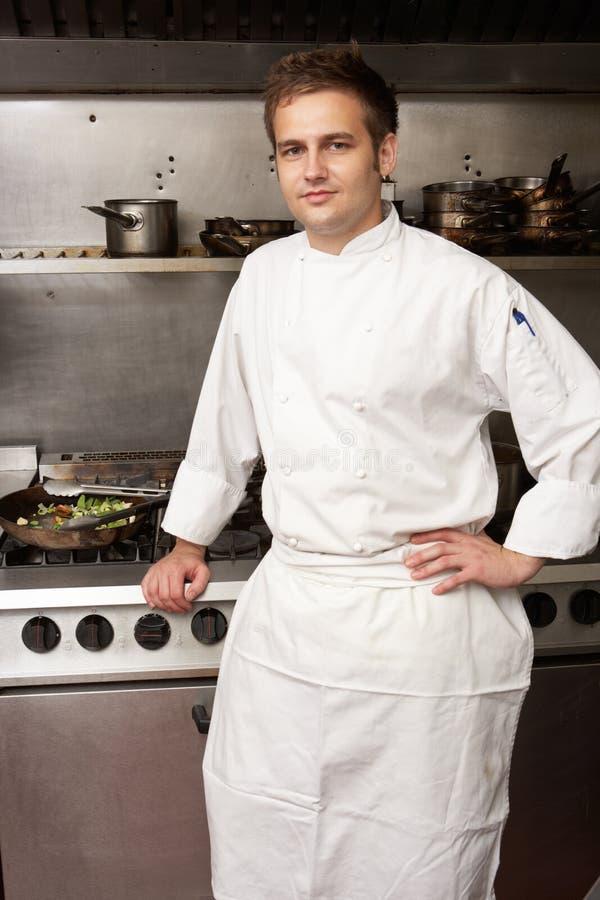 Mannelijke Chef-kok die zich naast Kooktoestel bevindt stock foto's