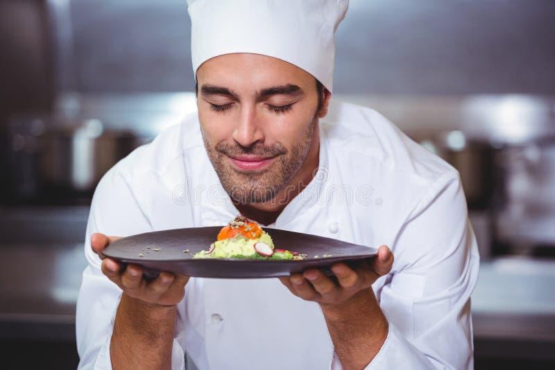 Mannelijke chef-kok met ogen gesloten ruikend voedsel stock afbeeldingen