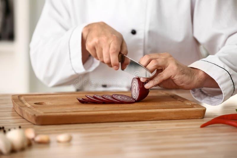 Mannelijke chef-kok scherpe ui in keuken, close-up royalty-vrije stock foto's